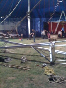 Here is the inside of the tent, with rehearsals going on before everything got finished.  That is the high wire platform in the foreground with the other pole crossing it.  Notice that the feet are already in position, the poles will be lifted, pivoting on their feet.